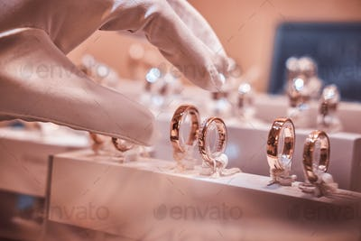 Hand in gloves takes to exclusive rings on the showcase of a jewelry store