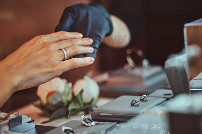 Girl tries on wedding ring in luxury jewelry store