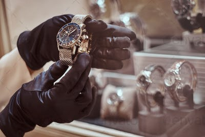 Close-up of the seller's hands in gloves shows the exclusive men's watch from the new collection