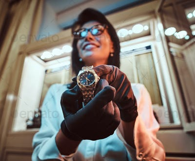 Seller shows an exclusive men's wristwatch from the new collection in the luxury jewelry store