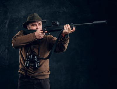 Portrait of a bearded hunter holding a rifle. Studio photo against dark wall background