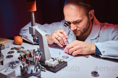 Expirienced watchmaker is doing engraving for custmer's watch at his workshop