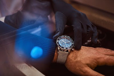 Assistant helps the client to try on exclusive men's watches, close-up hands.
