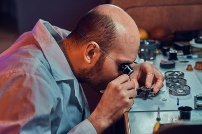 Pensive master is working on client's watch at his workshop.