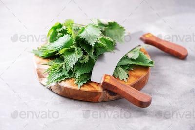Green nettle leaves in wooden pot on grey background. Alternative herbal medicine. Stinging nettles