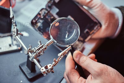 Technician carefully inspect the internal parts of the smartphone in a modern repair shop