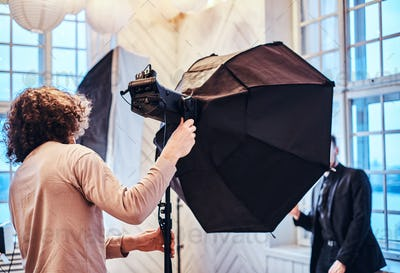 Photo of a curly photographer in a studio