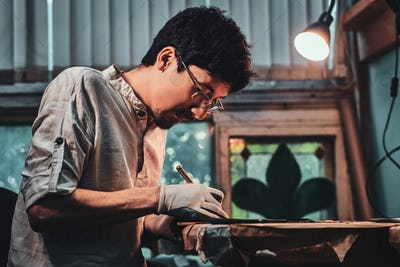 Expirienced diligent man is working on stained glass restoration