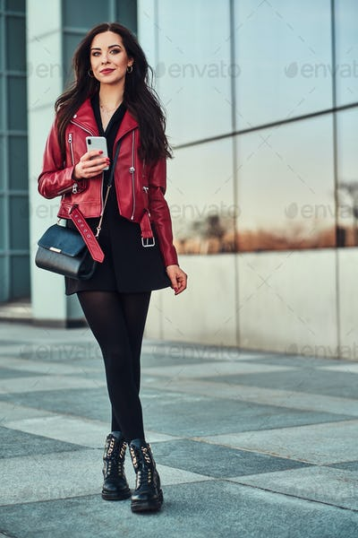 Attractive smiling woman in red jacket is posing near glass building