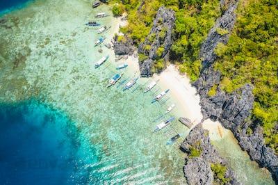 Aerial view of day trip boats moored at tropical Shimizu Island. Limestone coastal rocks, white sand