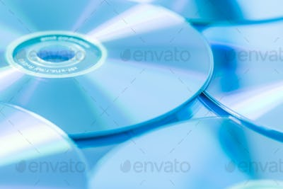 Stack of CD or DVD in blue tone as background. Soft focus.