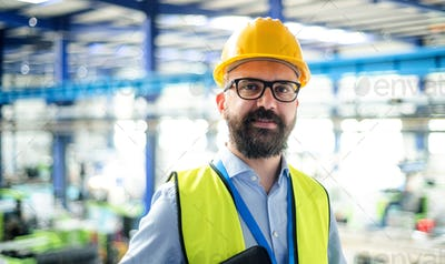 Front view of technician or engineer with hard hat standing in industrial factory