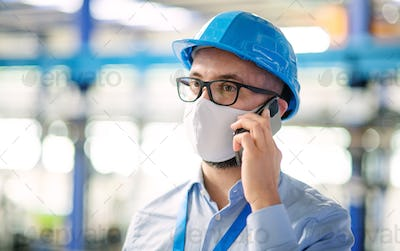 Technician or engineer with protective mask and telephone working in industrial factory