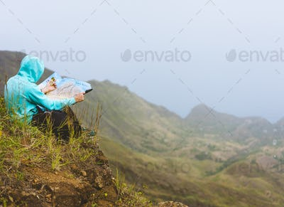 Traveler wear blue hoodie with the map sitting on the hill of a mountain in front of a gorgeous