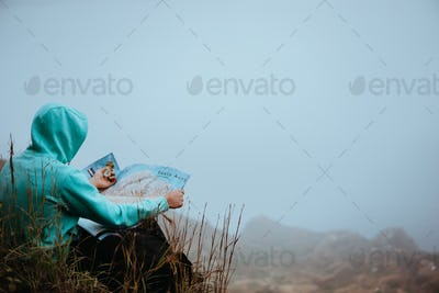 Traveler with a map sitting on the hill of a mountain in front of a gorgeous panorama view to the