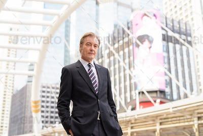 Mature handsome businessman wearing suit at skywalk bridge in the city