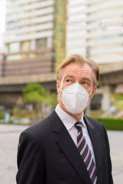 Mature businessman with mask thinking and looking up in the city outdoors