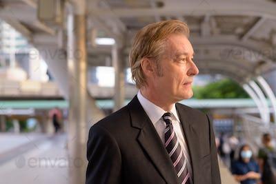 Mature handsome businessman in suit thinking at the footbridge