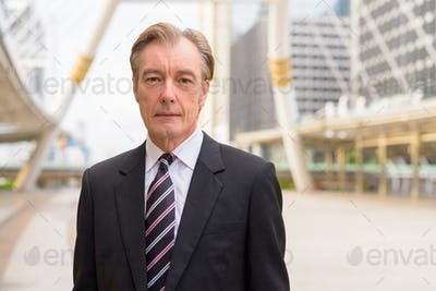 Mature handsome businessman in suit at skywalk bridge in the city