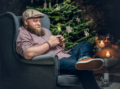 bearded male sits on a chair.
