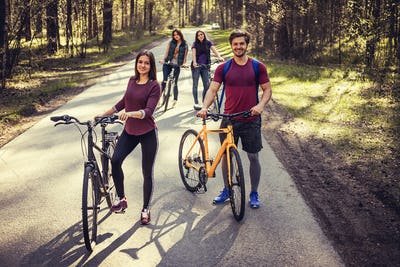 Four smiling adults with bicycles.