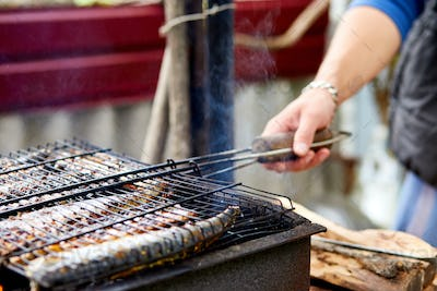 Men grilling fish mackerel on barbecue cooked on the grill in the open air flow