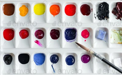 Plastic palette with colorful paints on a light grey bakground
