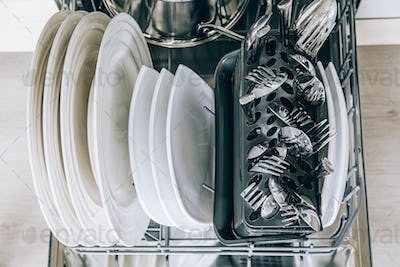 Open dishwasher with clean dishes close-up after washing.