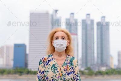 Portrait of blonde senior woman wearing mask for protection from corona virus outbreak against view