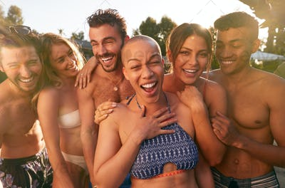 Portrait Of Group Of Friends Outdoors Relaxing By Swimming Pool And Enjoying Summer Party