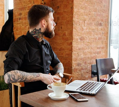 Male with beard sitting in caffee shop and looking through a window