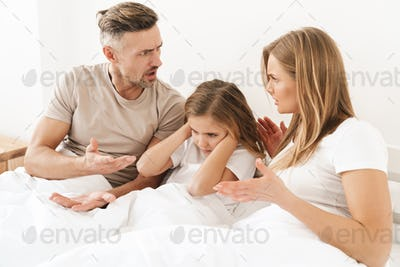 Photo of parents fighting while sitting with unhappy daughter