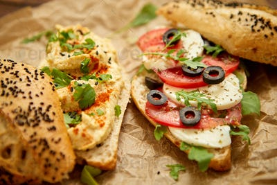 Two delicious sandwiches with hummus, tomato, mozarella cheese, herbs and olives