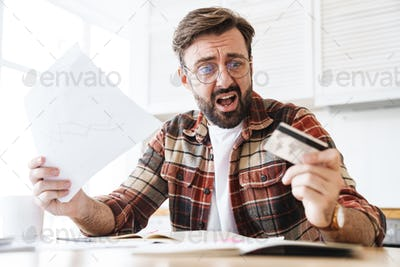 Portrait of shocked man holding credit card and papers while working