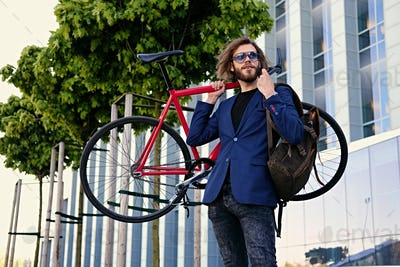 A man holds red single speed bicycle on his shoulder.