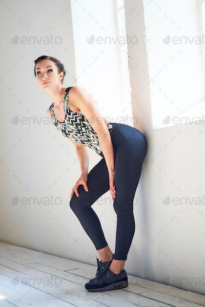 Portrait of slim athletic brunette female wearing black sportswear.