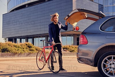 A man puts fixed bicycle in the car's trunk.