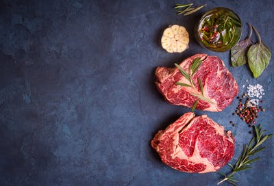 Raw meat steak on rustic concrete background ready to roasting