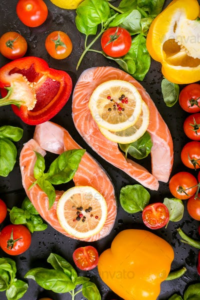 Raw salmon steaks and fresh ingredients for cooking