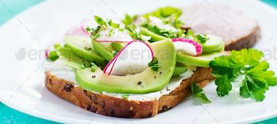 Tasty breakfast. Healthy avocado toast and radish on whole grain bread and baked sliced meat.