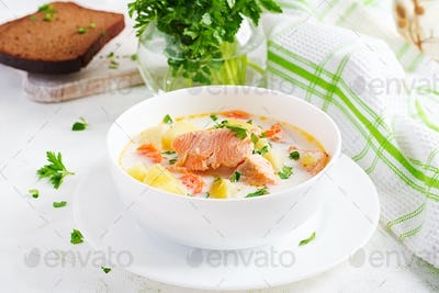 Creamy soup with salmon, potatoes, onions and carrots and  in a bowl.