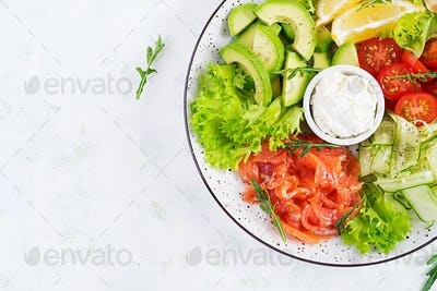 Salad of salted fish salmon, avocado, cherry tomatoes, cucumber, lettuce