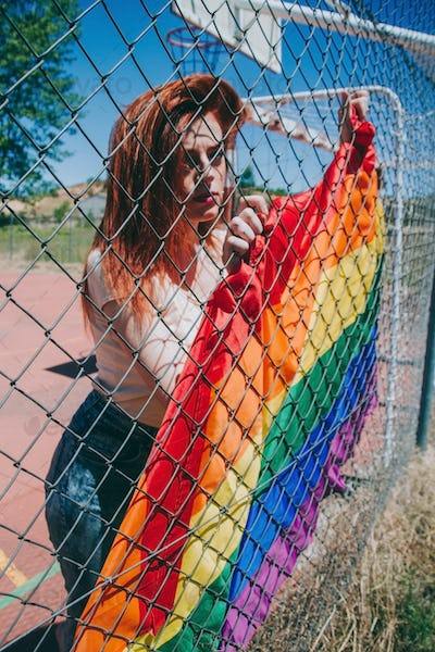 Young sad woman covering by a rain bow flag