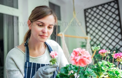 Woman looking at flowers on balcony checking for pests and diseases