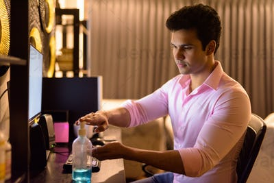 Young handsome Indian businessman using hand sanitizer while working overtime at home during