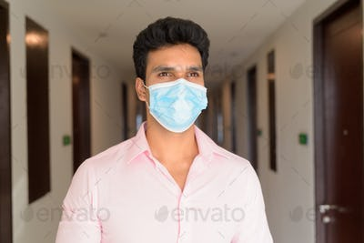 Face of young Indian businessman wearing mask and thinking in the corridor