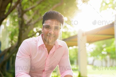 Happy young handsome Indian businessman with face shield smiling at the park