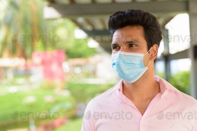 Face of young Indian businessman wearing mask and thinking at the park