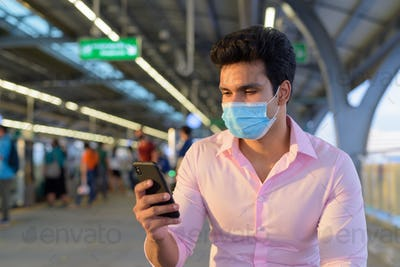 Young Indian businessman wearing mask and sitting with distance while using phone at the skytrain