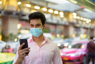 Young Indian businessman with mask using phone in the city streets